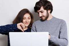 People, technology and communication concept. Stylish bearded guy and his girlfriend using laptop and browsing internet for online. Shopping choosing some Stock Images
