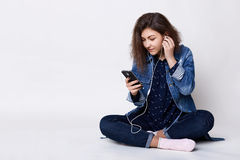 People, technology and communication. A pretty young dark-haired girl listening to the music with her cell-phone holding her hand Stock Photo