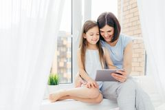 People, technology, family, children concept. Positive young other and her small daughter sit on window sill, hold digital tablet,. Watch interesting cartoon royalty free stock image