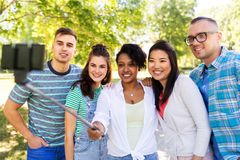 Happy friends taking photo by selfie stick at park royalty free stock photos