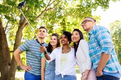 Happy friends taking photo by selfie stick at park stock photo