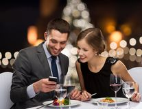 Smiling couple eating main course at restaurant. People, technology and holiday concept - smiling couple taking picture of main course with smartphone camera at stock image