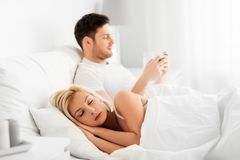 Man using smartphone while woman is sleeping. People, technology, internet addiction and cheating concept - men using smartphone while his wife or girlfriend is royalty free stock photo