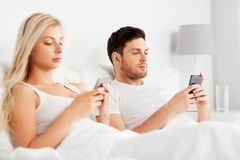 Couple with smartphones in bed. People, technology, internet addiction and communication concept - couple with smartphones in bed royalty free stock photography