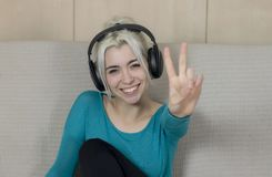 Happy blonde young woman sitting on sofa with headphones listeni stock photos