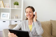 Happy woman with tablet pc and headphones at home Stock Image