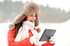 Woman in winter fur hat with tablet pc outdoors Stock Image