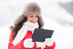 Woman in winter fur hat with tablet pc outdoors Royalty Free Stock Photography