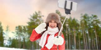 Happy woman taking selfie over winter forest stock images