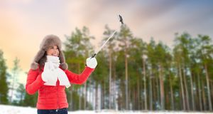 Happy woman taking selfie over winter forest stock photography