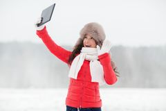 Woman in winter fur hat with tablet pc outdoors Stock Images