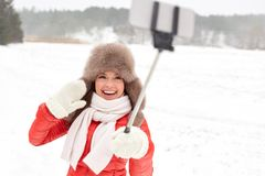Happy woman with selfie stick outdoors in winter Royalty Free Stock Photos