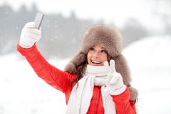 Happy woman taking selfie outdoors in winter Stock Images