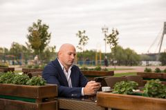 People, technology, leisure and lifestyle - bald man with smartphone texting message at city street cafe royalty free stock photos