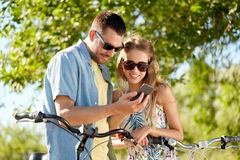 Happy couple with bicycles and smartphone outdoors Stock Photos