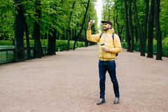 People, technology, lifestyle and relaxation concept. Handsome man wearing yellow jacket, black cap and jeans standing in park dri. Nking coffee and making royalty free stock photo