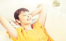 Happy asian woman with earphones listening music. People, technology, relax and leisure concept - happy asian young woman lying on sofa with earphones listening Royalty Free Stock Photos