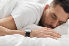 Close up of man with smart watch sleeping in bed stock photos