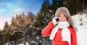 Woman calling on smartphone over winter forest stock photo