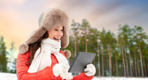Woman in fur hat with tablet pc over winter forest royalty free stock image
