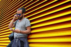 Man with earphones and smartphone over wall Stock Photo