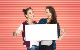Happy teenage girls or friends holding white board royalty free stock photo