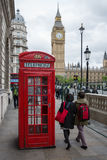People and telephone booth near Big Ben in London, UK. LONDON, ENGLAND - JUNE 08, 2017: People and call box at Parliament square near Big Ben in London, UK Stock Photo