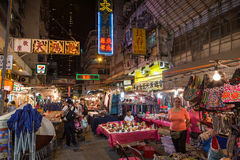 People at the Temple Street Night Market in Hong Kong at night. Tables and stalls full of all kinds of cheap merchandise being sold at the Temple Street Night Stock Photography