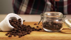 People throw roast coffee bean in jar slowmotion closeup, fill container arabica. People throw roasted coffee bean in jar slowmotion closeup, fill container stock video footage