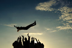 People throwing girl in the air Stock Photos