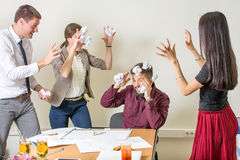 People throwing papers on a colleague Stock Photos