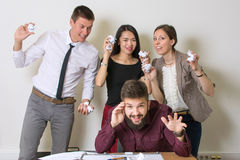 People throwing papers on a colleague Royalty Free Stock Photos