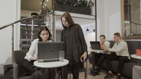 People thumb up to the camera in the co-working space. Young attractive workers sit in the co-working space at the table. Two women discuss their work at laptop stock video footage