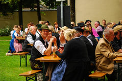 People in tipical bavarian attire sit during an event. Onlookers sit at banks during an event called Köcherl Ball in Neuötting,Germany Stock Images