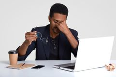 People and tiredness concept. Fatigue black African American man takes off spectacles, feels sleepy and overworked, surrounded. With modern technologies stock image