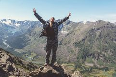 People tively in the form of standing on the edge. A tourist raised his hands to the sky reveal the joy of conquering the mountain peaks. People tively in the Royalty Free Stock Photos