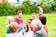 People toasting at party, in the background man at grill Stock Photography