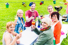 People toasting at party, in the background man at grill royalty free stock photo