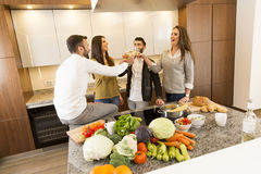 People toasting with white wine in the kitchen. Young people toasting with white wine in the kitchen Stock Photography