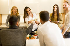 People toasting white wine in modern kitchen Royalty Free Stock Images