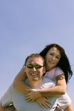 People - Together. Man carrying a woman piggy back. Blue sky as a background Stock Photo