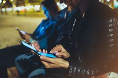 People together pointing finger on screen smartphone on background bokeh light in night atmospheric city, group adult hipsters. Friends using in hands modern royalty free stock photo