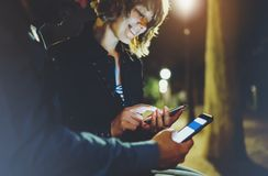 People together pointing finger on screen smartphone on background bokeh light in night atmospheric city, group adult hipsters royalty free stock photography