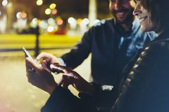 People together pointing finger on screen smartphone on background bokeh light in night atmospheric city, group adult hipsters royalty free stock images