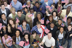 People Together Raising American Flag. High angle view of people raising American flags Royalty Free Stock Images