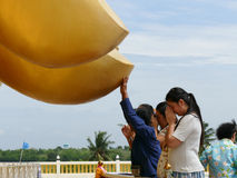 People touch finger of the big golden buddha statue Royalty Free Stock Photography