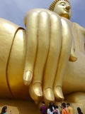 People touch finger of the big golden buddha statue Stock Photography