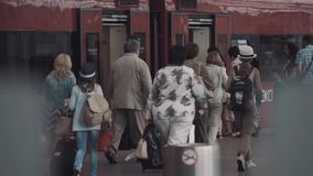 People tourists crowd enters red train open doors at station. Middle aged people tourists crowd with kids enters red train open doors at railroad station stock video footage