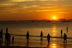 People, tourists enjoy a gorgeous sunset on a tropical beach. Silhouettes of people are all watching the sun. Golden tones. The. Path on the water stock photos