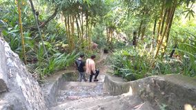 People tourists go down ancient stone stairs on hill slope. DANANG/VIETNAM - MAY 05 2018: View above middle aged people going down large ancient stone stairs stock footage